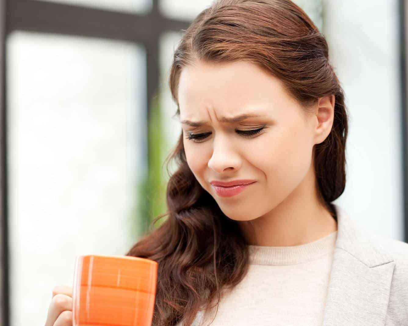 Concerned look on woman's face while looking into mug