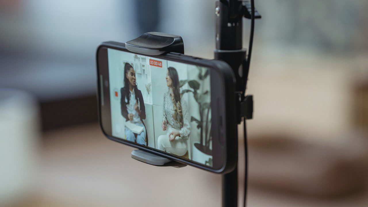Influencer Marketing shown through the back of a smartphone on a tripod as it is capturing video of two women talking to camera.