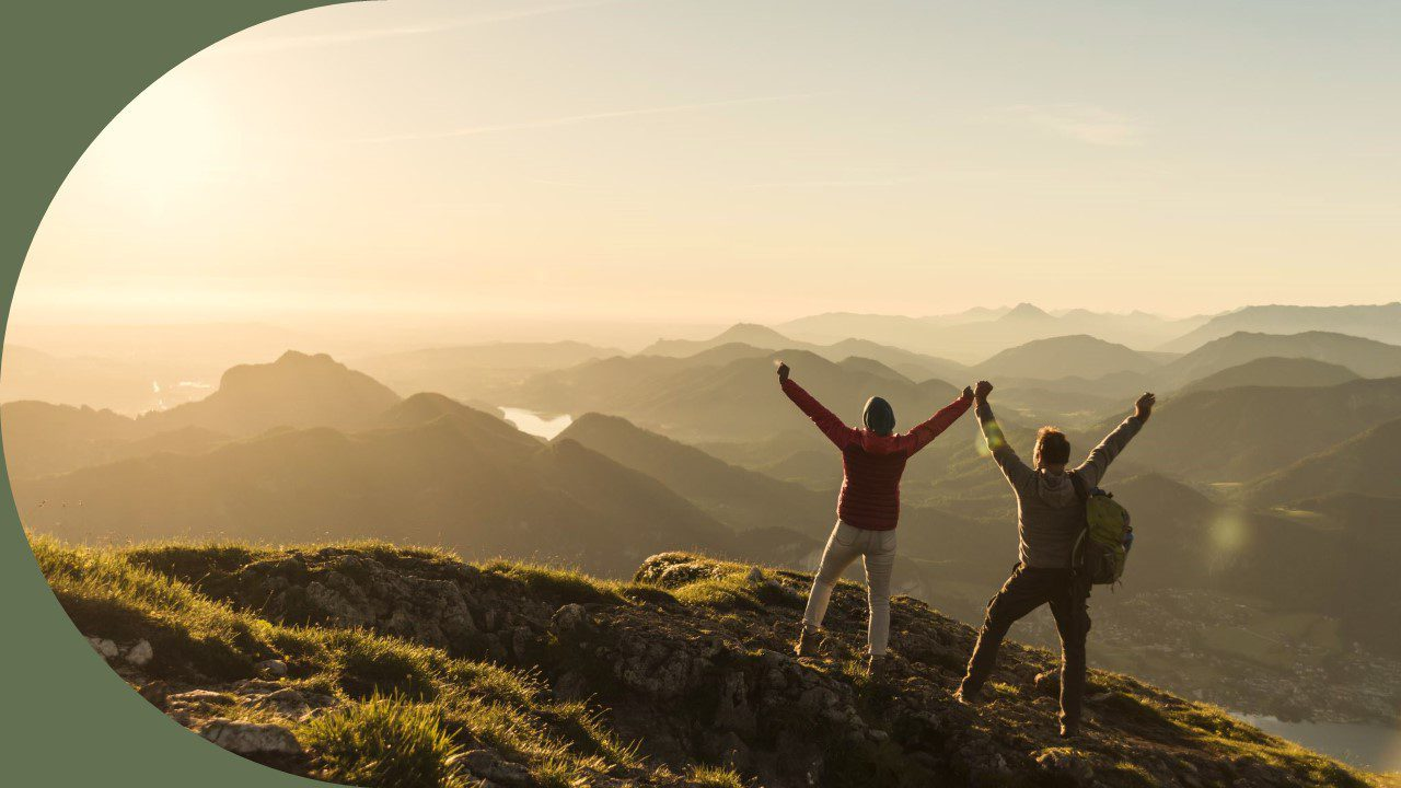 Two hikers on top of a mountain facing away from the camera and posing as by throwing their hands up in a cheering motion. They both look excited, relieved, and proud to have made the journey.